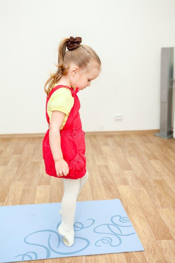 Λίγο παιδί που περπατά tiptoe πέρα από το αθλητικό χαλί στοκ φωτογραφία με δικαίωμα ελεύθερης χρήσης