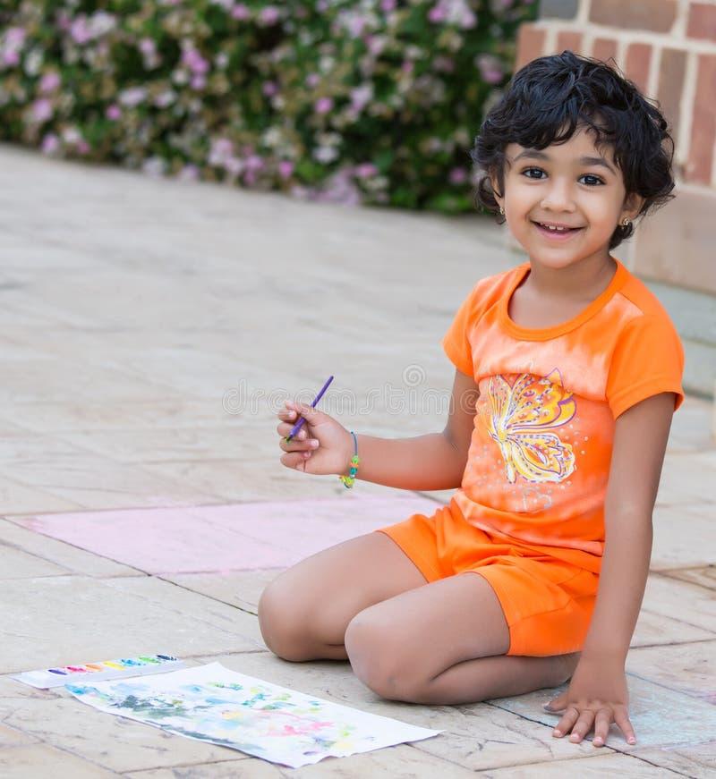 Λίγο παιδί που χρωματίζει σε ένα Patio στοκ φωτογραφία