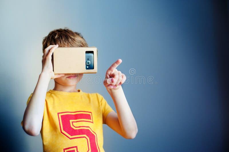 Λίγο παιδί χρησιμοποιεί το χαρτόνι εικονικής πραγματικότητας VR στο μπλε υπόβαθρο στοκ εικόνες με δικαίωμα ελεύθερης χρήσης