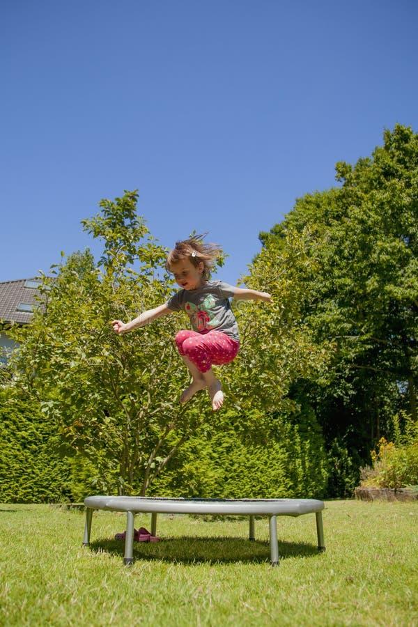 Λίγο πολύ ευτυχές χαριτωμένο κορίτσι παιδιών που αναπηδά σε ένα τραμπολίνο στοκ φωτογραφία με δικαίωμα ελεύθερης χρήσης