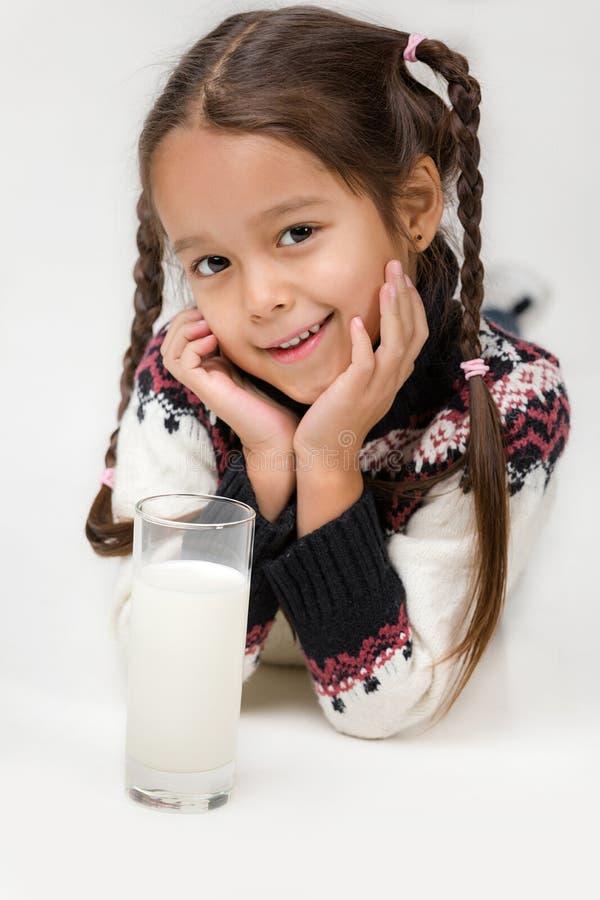 Λίγο ποτήρι εκμετάλλευσης κοριτσιών παιδιών του γάλακτος στο άσπρο υπόβαθρο στοκ φωτογραφίες