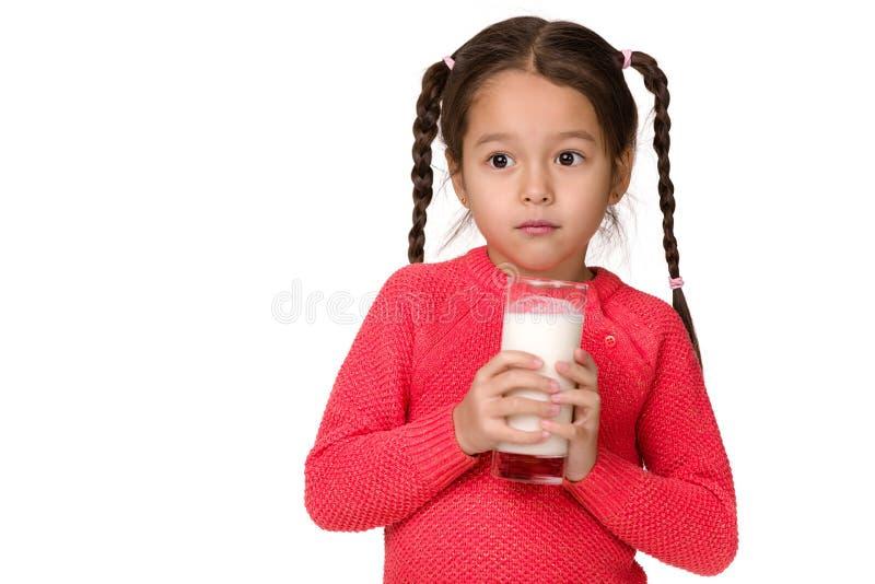 Λίγο ποτήρι εκμετάλλευσης κοριτσιών παιδιών του γάλακτος στο άσπρο υπόβαθρο στοκ φωτογραφίες με δικαίωμα ελεύθερης χρήσης