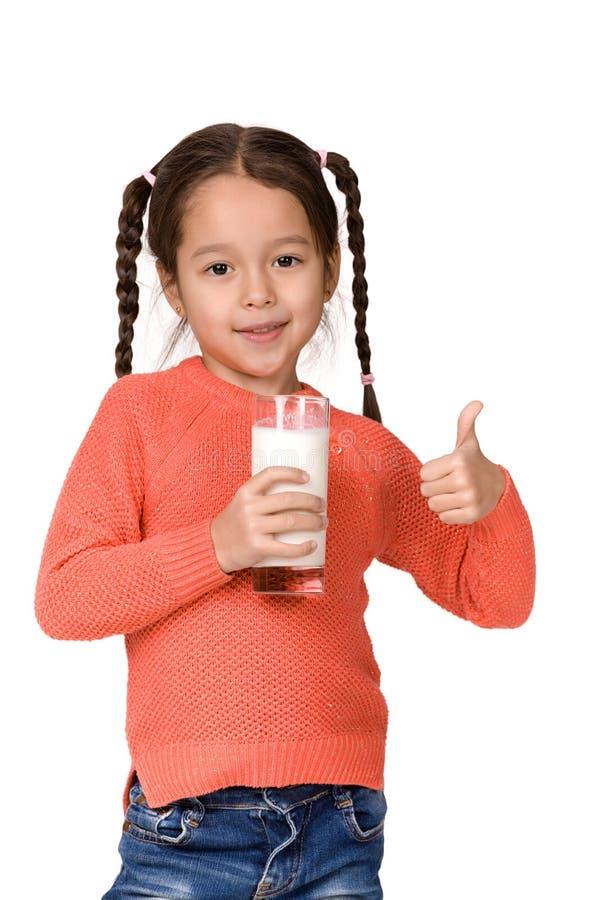 Λίγο ποτήρι εκμετάλλευσης κοριτσιών παιδιών του γάλακτος στο άσπρο υπόβαθρο στοκ φωτογραφία