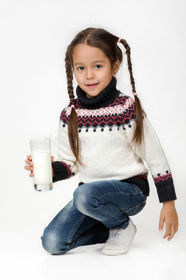Λίγο ποτήρι εκμετάλλευσης κοριτσιών παιδιών του γάλακτος στο άσπρο υπόβαθρο στοκ εικόνες