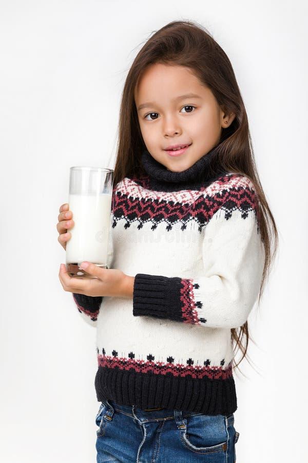 Λίγο ποτήρι εκμετάλλευσης κοριτσιών παιδιών του γάλακτος στο άσπρο υπόβαθρο στοκ εικόνα