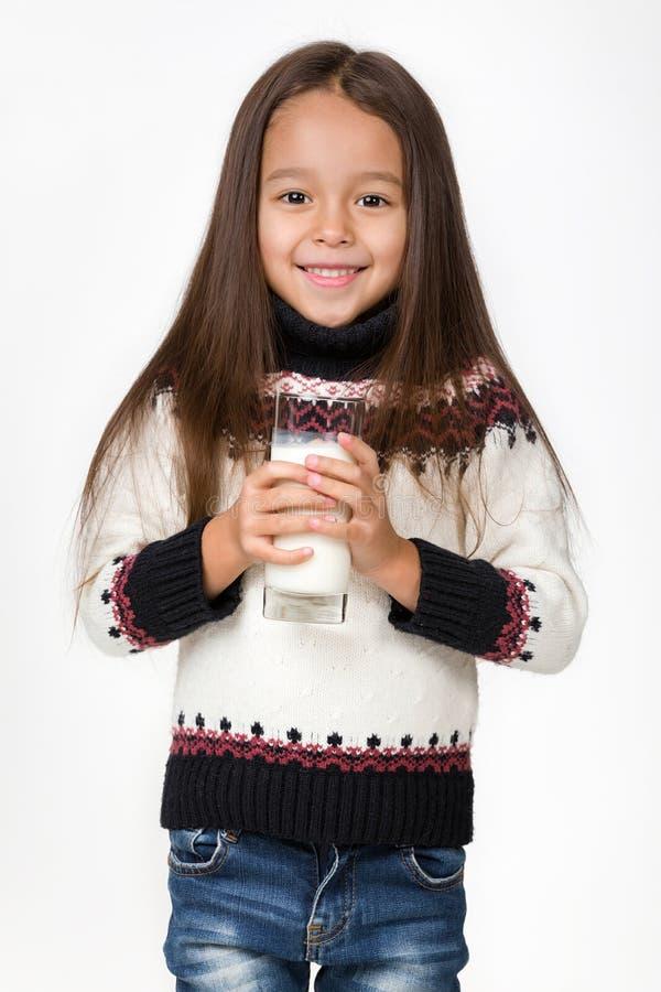 Λίγο ποτήρι εκμετάλλευσης κοριτσιών παιδιών του γάλακτος στο άσπρο υπόβαθρο στοκ εικόνα με δικαίωμα ελεύθερης χρήσης