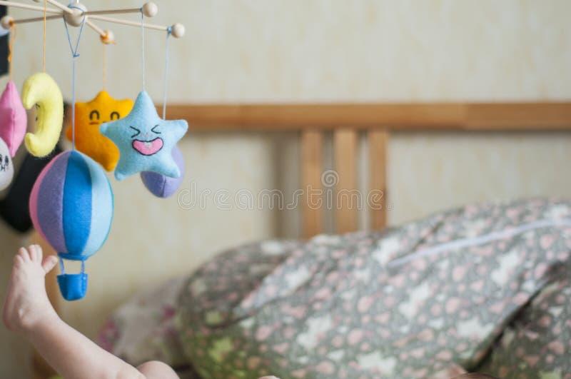 Λίγο πόδι Μωρό στο κρεβάτι γονέων Ζωηρόχρωμα και αστεία κινητά παιχνίδια στοκ εικόνες