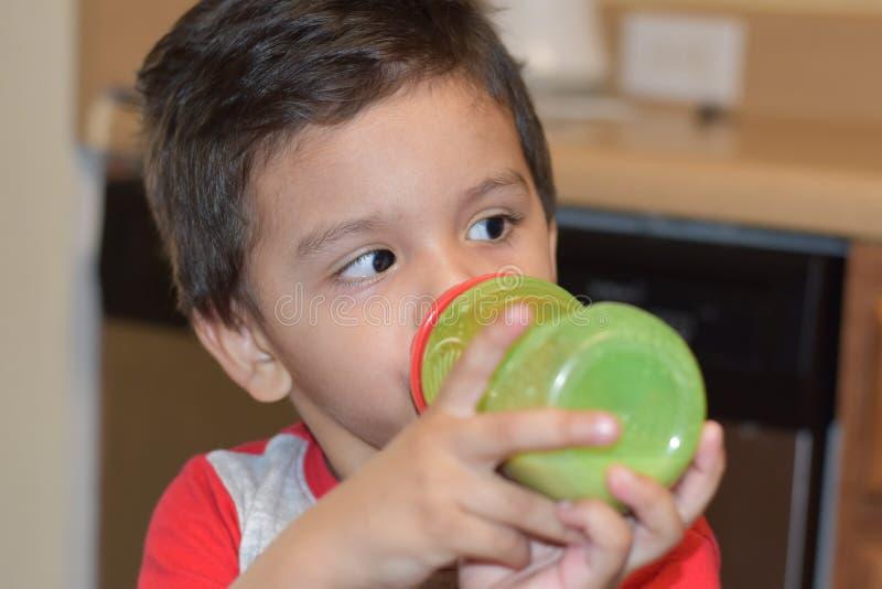 Λίγο πόσιμο γάλα αγοράκι στο πράσινο μπουκάλι του στοκ φωτογραφία με δικαίωμα ελεύθερης χρήσης