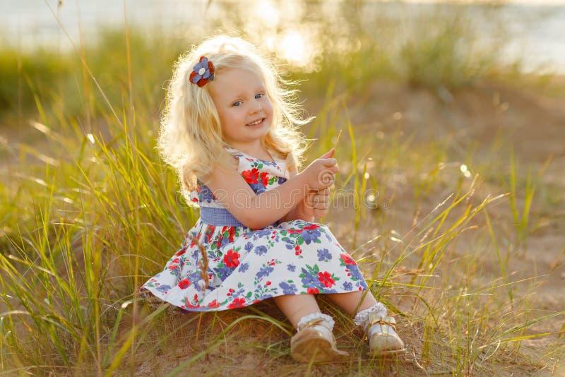 Λίγο σγουρό ξανθό κορίτσι κάθεται και χαμογελά στην άμμο και τη χλόη στο SU στοκ φωτογραφία