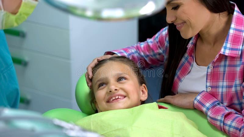 Λίγο συμπαθητικό κορίτσι που χαμογελά στον επαγγελματικό παιδιατρικό οδοντίατρο πριν από τη διαδικασία στοκ εικόνες
