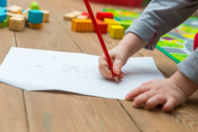 Λίγο σχέδιο παιδιών με το μολύβι στη Λευκή Βίβλο στοκ εικόνες με δικαίωμα ελεύθερης χρήσης