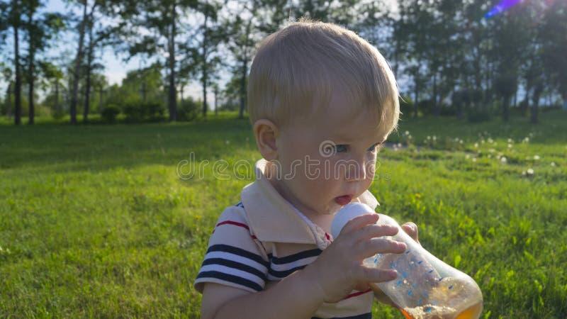 Λίγο τσάι κατανάλωσης αγοριών από ένα μπουκάλι στοκ εικόνες με δικαίωμα ελεύθερης χρήσης