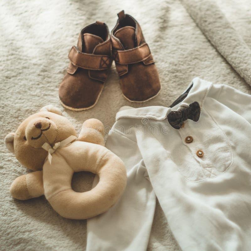 Λίγο χέρι - γίνοντα ενδύματα μωρών Φωτογραφία του υπερήχου νεογέννητα ενδύματα στο μπεζ μάλλινο υπόβαθρο στοκ φωτογραφία με δικαίωμα ελεύθερης χρήσης
