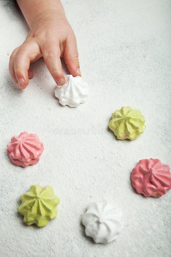 Λίγο χέρι μωρών παίρνει ένα γαλλικό γλυκό επιδόρπιο μαρέγκας σε ένα άσπρο αναδρομικό υπόβαθρο, κάθετα στοκ φωτογραφίες