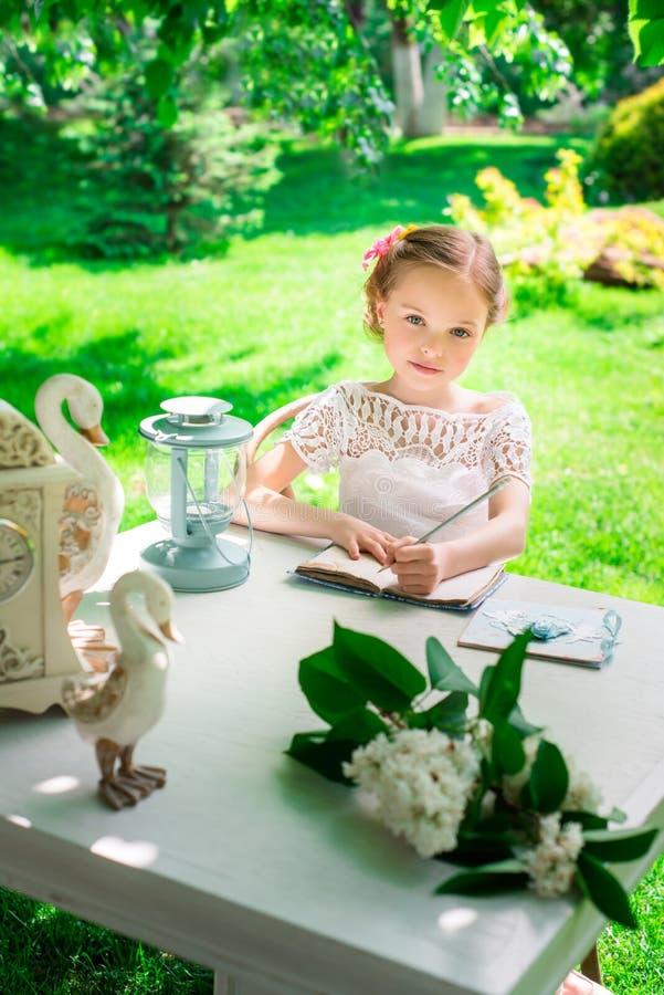Λίγο χαμογελώντας κορίτσι που γράφει στο σημειωματάριο υπαίθριο στο πάρκο VI στοκ φωτογραφία