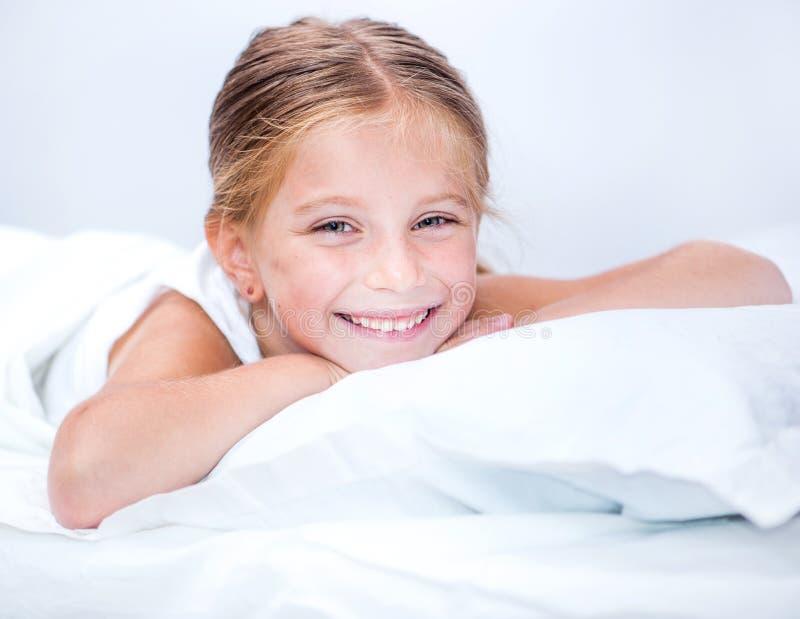 Λίγο χαμογελώντας κορίτσι σε ένα κρεβάτι στοκ φωτογραφίες