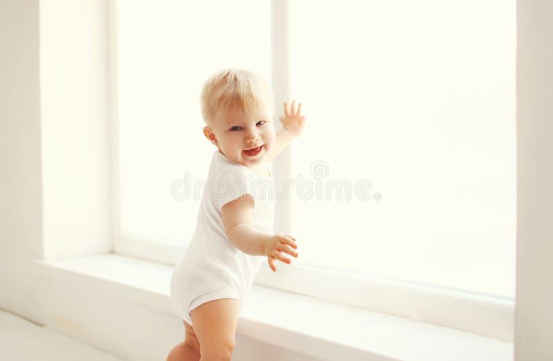 Λίγο χαμογελώντας μωρό στο άσπρο σπίτι δωματίων στέκεται κοντά στο παράθυρο στοκ φωτογραφίες