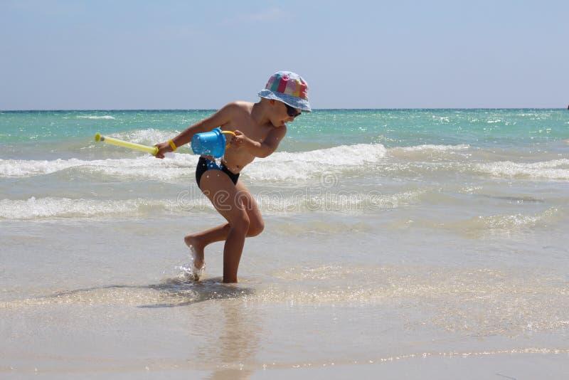 Λίγο χαριτωμένα τρεξίματα αγοριών κατά μήκος της παραλίας και των παιχνιδιών στοκ φωτογραφίες