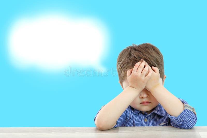 Λίγο χαριτωμένο αγόρι και το σύννεφο σκέψεών του στο υπόβαθρο στοκ φωτογραφία