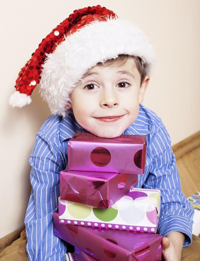 Λίγο χαριτωμένο αγόρι με τα δώρα Χριστουγέννων στο σπίτι κλείστε επάνω το συναισθηματικό πρόσωπο στα κιβώτια στο κόκκινο καπέλο s στοκ εικόνα