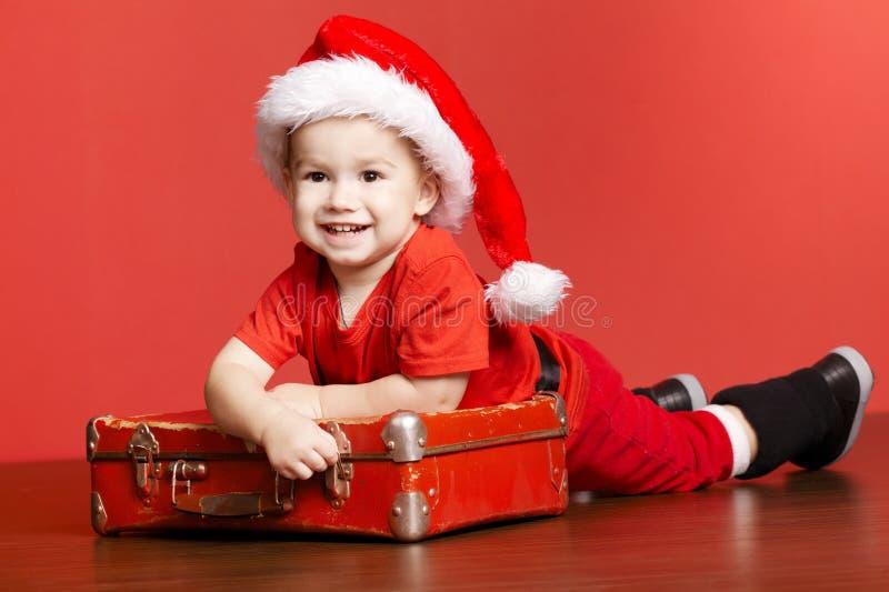 Λίγο χαριτωμένο αγόρι με την κόκκινη βαλίτσα στοκ εικόνες