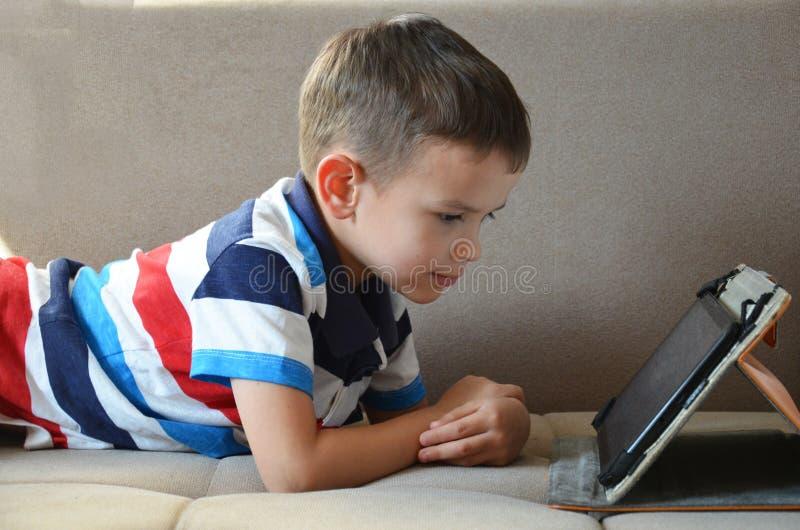 Λίγο χαριτωμένο αγόρι παίζοντας παιχνίδια στα πράσινα μπλουζών στα κινούμενα σχέδια ταμπλετών και προσοχής Μικρό παιδί με την ταμ στοκ φωτογραφίες με δικαίωμα ελεύθερης χρήσης