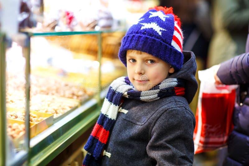 Λίγο χαριτωμένο αγόρι παιδιών κοντά στη γλυκιά στάση με το μελόψωμο και τα καρύδια Ευτυχές παιδί στην αγορά Χριστουγέννων στη Γερ στοκ εικόνες με δικαίωμα ελεύθερης χρήσης