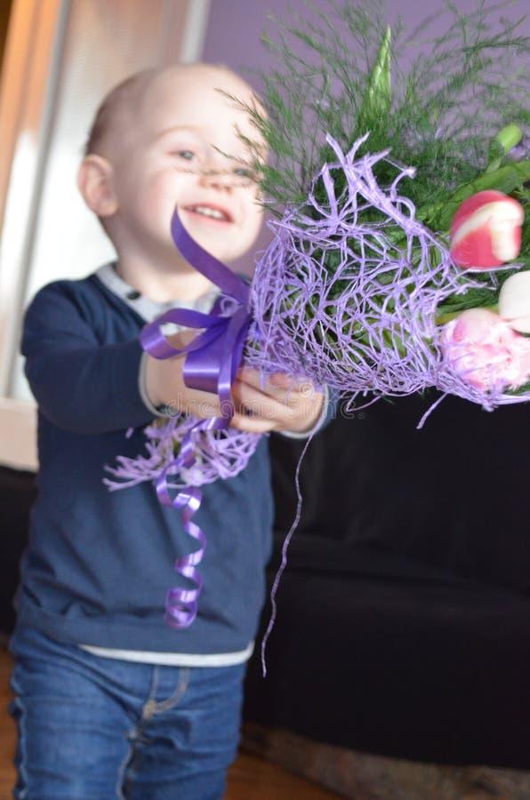 Λίγο χαριτωμένο αγόρι που δίνει τα λουλούδια στοκ εικόνα