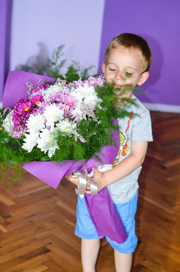 Λίγο χαριτωμένο αγόρι που δίνει τα λουλούδια στοκ εικόνες