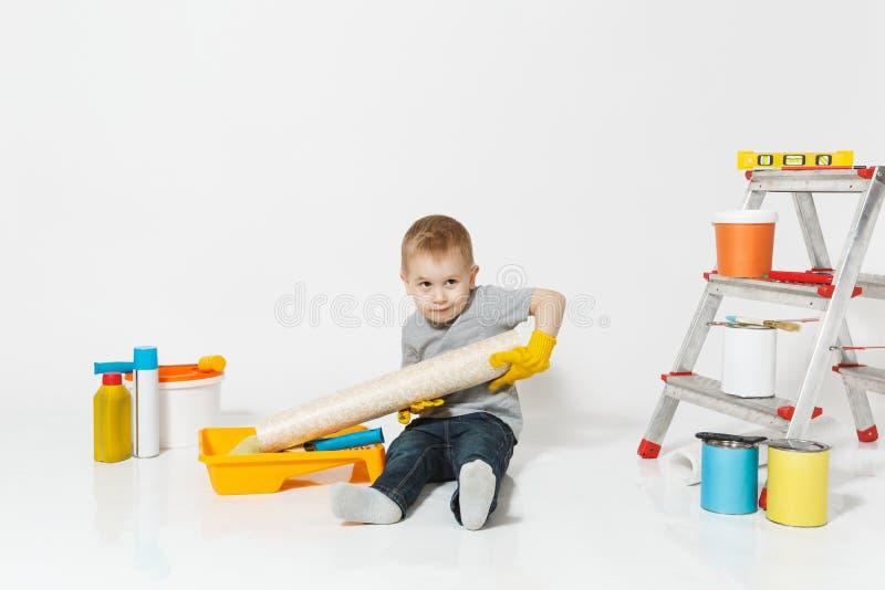 Λίγο χαριτωμένο αγόρι στα κίτρινα γάντια με τα όργανα για το δωμάτιο διαμερισμάτων ανακαίνισης που απομονώνεται στο άσπρο υπόβαθρ στοκ εικόνες