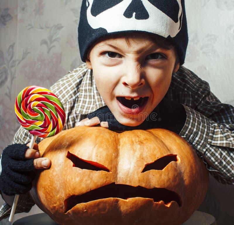 Λίγο χαριτωμένο αγόρι στο καπέλο σκελετών με την κολοκύθα και καραμέλα στις διακοπές κομμάτων αποκριών, έννοια ανθρώπων τρόπου ζω στοκ φωτογραφία
