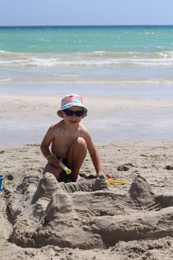 Λίγο χαριτωμένο αγόρι χτίζει ένα κάστρο άμμου Σπίτι της άμμου στην παραλία στοκ φωτογραφίες