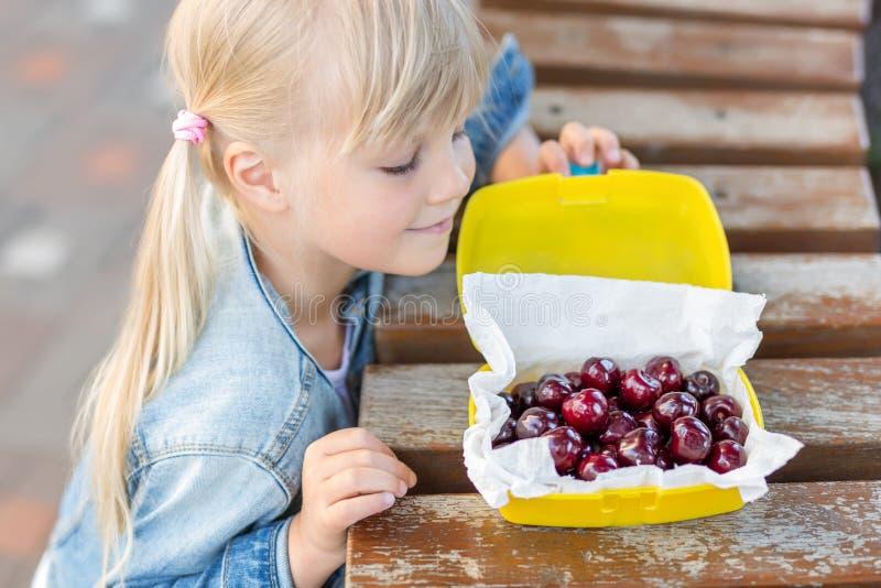 Λίγο χαριτωμένο καυκάσιο ξανθό κορίτσι που εξετάζει το καλαθάκι με φαγητό με τα φρέσκα νόστιμα γλυκά κεράσια στον ξύλινο πίνακα υ στοκ εικόνα με δικαίωμα ελεύθερης χρήσης