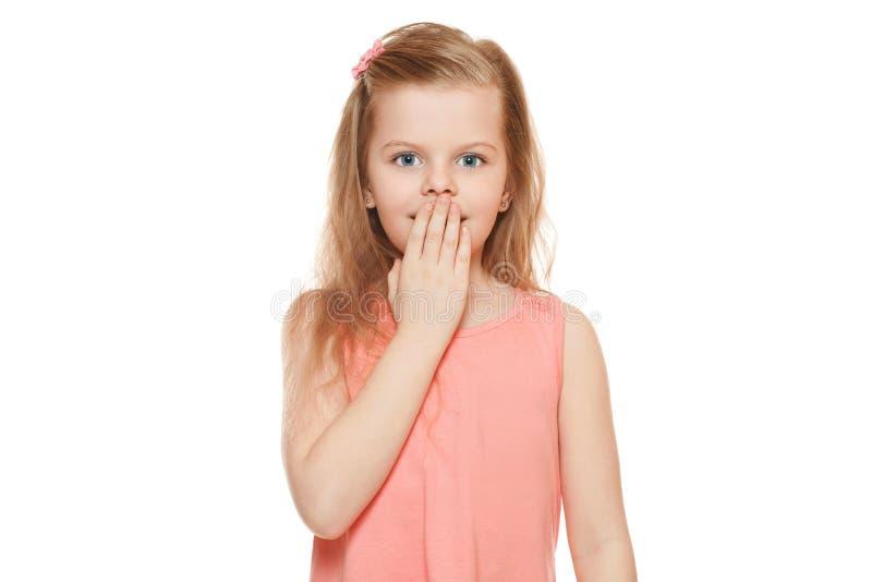 Λίγο χαριτωμένο κορίτσι έκπληκτο κλείσιμο του στόματός της, που απομονώνεται στο άσπρο υπόβαθρο στοκ φωτογραφία