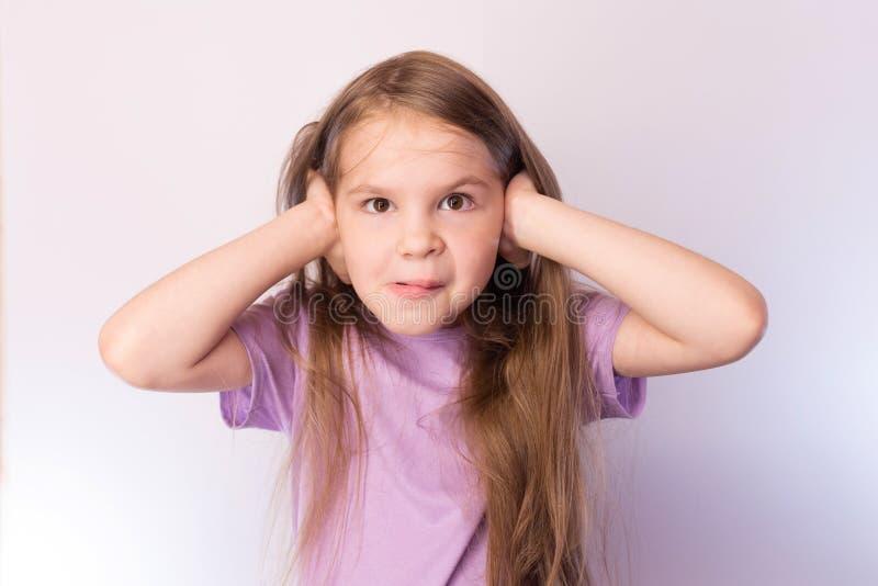 Λίγο χαριτωμένο κορίτσι έχει κλείσει τα αυτιά του με τα χέρια του, με μια αστεία έκφραση στο πρόσωπό του, σε ένα ελαφρύ υπόβαθρο στοκ φωτογραφία με δικαίωμα ελεύθερης χρήσης