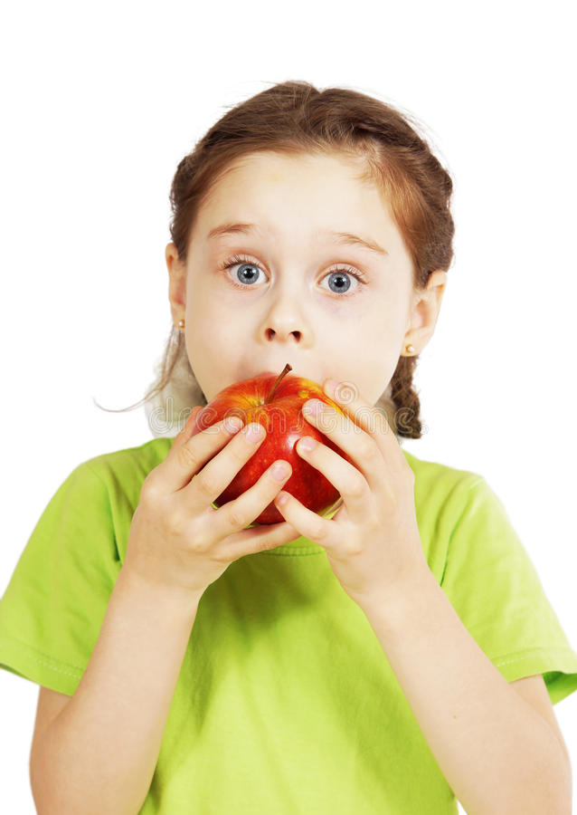 Λίγο χαριτωμένο κορίτσι δαγκώνει ένα μεγάλο κόκκινο μήλο με την όρεξη στοκ φωτογραφίες