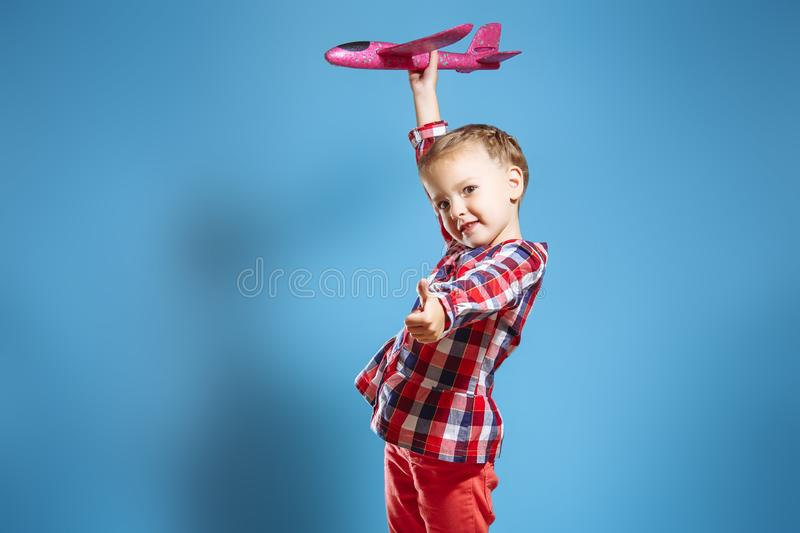 Λίγο χαριτωμένο κορίτσι με ένα αεροπλάνο παιχνιδιών που παρουσιάζει αντίχειρά της στοκ εικόνα