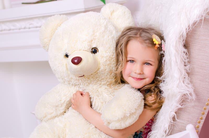 Λίγο χαριτωμένο κορίτσι με μεγάλο άσπρο teddy αντέχει στοκ εικόνα