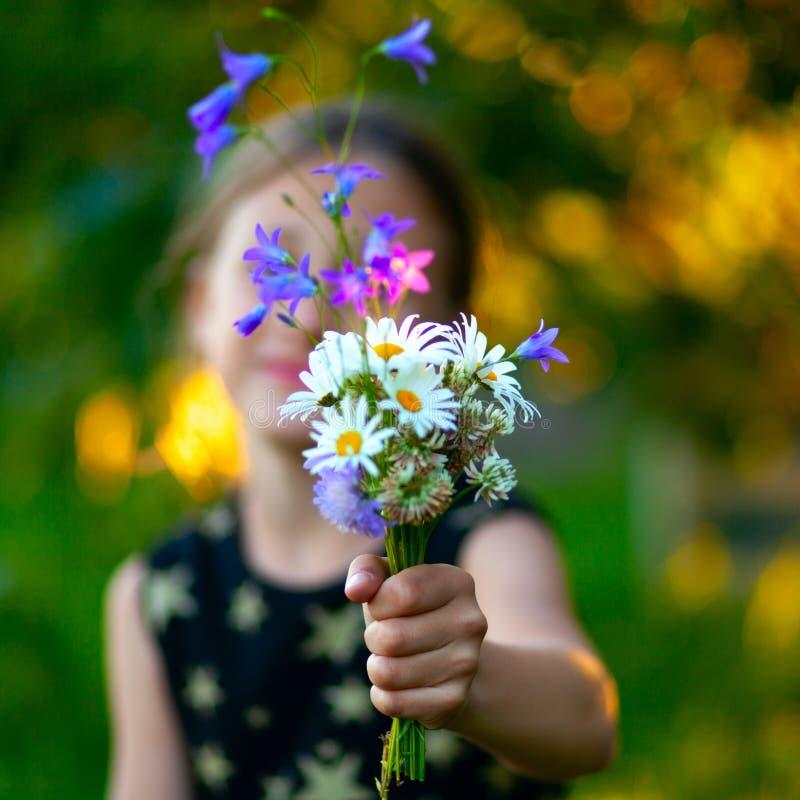 Λίγο χαριτωμένο κορίτσι με την ανθοδέσμη των wildflowers Το παιδί δίνει τα λουλούδια στο mom Κλείστε επάνω την άποψη σε ετοιμότητ στοκ φωτογραφία με δικαίωμα ελεύθερης χρήσης