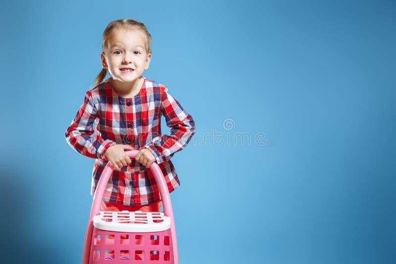 Λίγο χαριτωμένο κορίτσι με τη βαλίτσα παιχνιδιών στο μπλε υπόβαθρο στοκ εικόνες με δικαίωμα ελεύθερης χρήσης