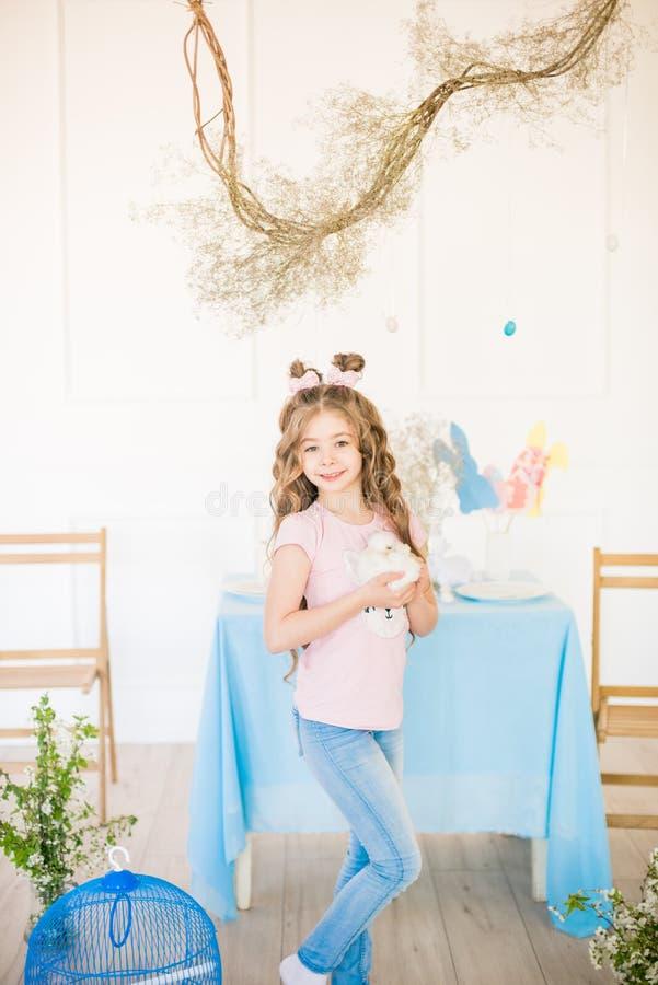 Λίγο χαριτωμένο κορίτσι με τη μακριά σγουρή τρίχα με τα μικρά λαγουδάκια και ντεκόρ Πάσχας στο σπίτι στον πίνακα στοκ εικόνες