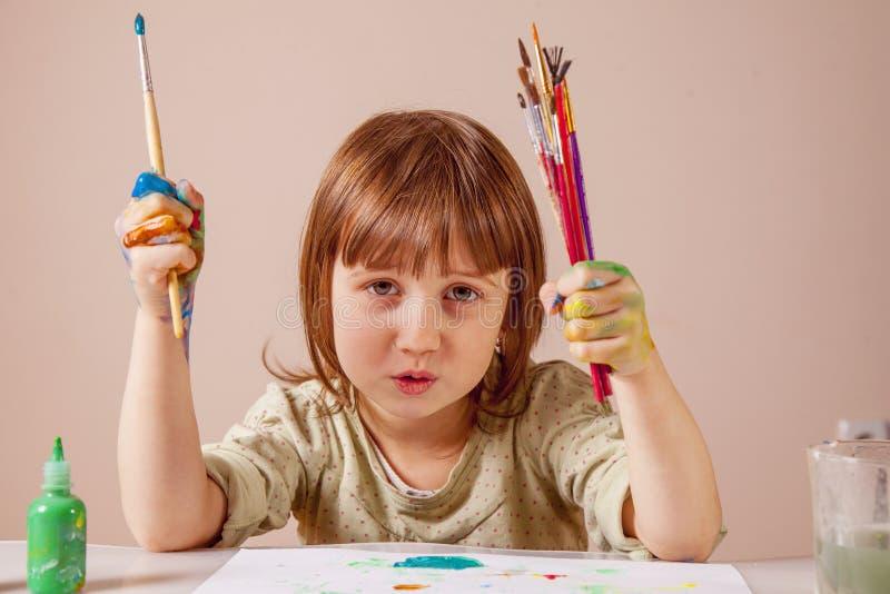 Λίγο χαριτωμένο κορίτσι παιδιών που χρωματίζει με τις βούρτσες Τέχνη, δημιουργικότητα, έννοια παιδικής ηλικίας ομορφιάς στοκ εικόνα