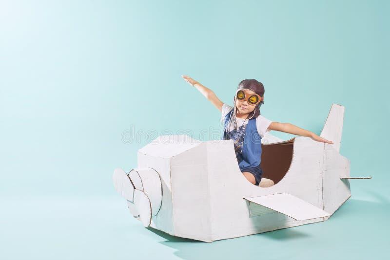 Λίγο χαριτωμένο κορίτσι που παίζει με ένα αεροπλάνο χαρτονιού στοκ φωτογραφία