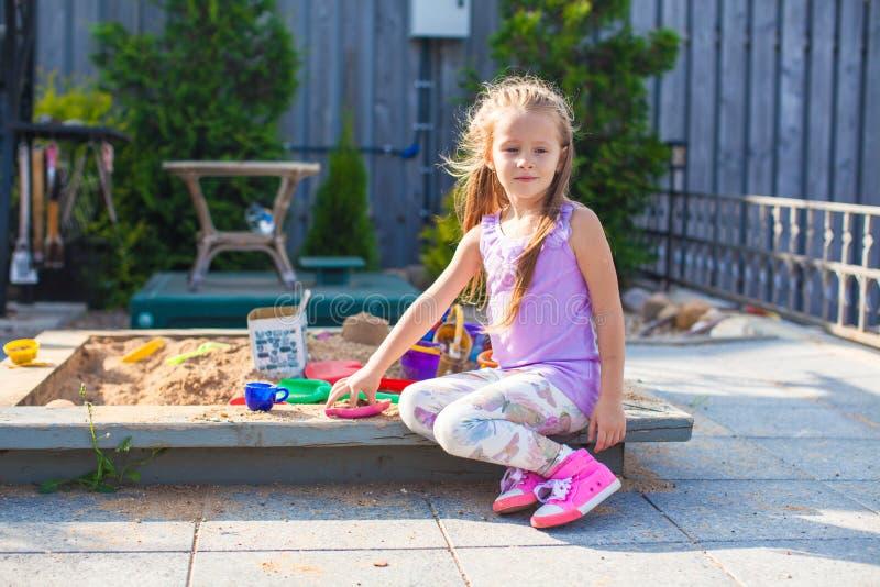 Λίγο χαριτωμένο κορίτσι που παίζει στο Sandbox με τα παιχνίδια στοκ εικόνες