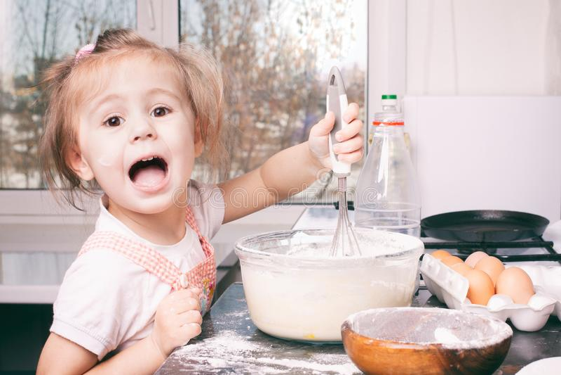 Λίγο χαριτωμένο κορίτσι που προετοιμάζει τη ζύμη στην κουζίνα στο σπίτι στοκ εικόνες