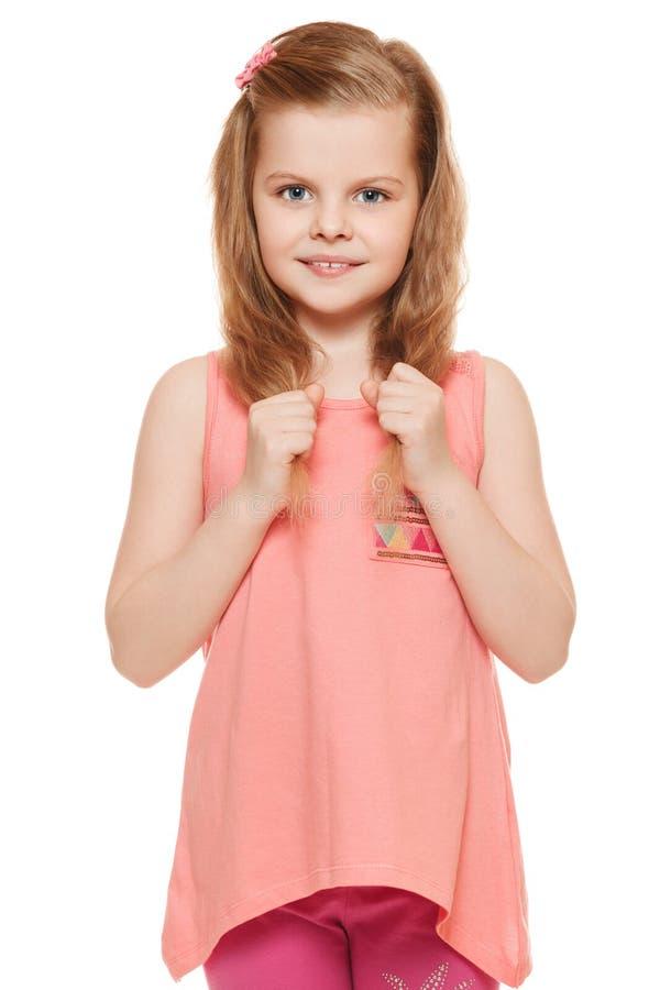 Λίγο χαριτωμένο κορίτσι σε ένα ρόδινο πουκάμισο κρατά την τρίχα χεριών, που απομονώνεται στο άσπρο υπόβαθρο στοκ εικόνες με δικαίωμα ελεύθερης χρήσης