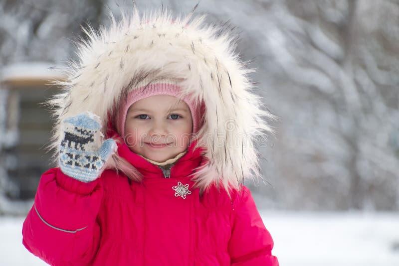 Λίγο χαριτωμένο κορίτσι σε μια μεγάλη κουκούλα γουνών που κυματίζει το χέρι της στοκ φωτογραφία