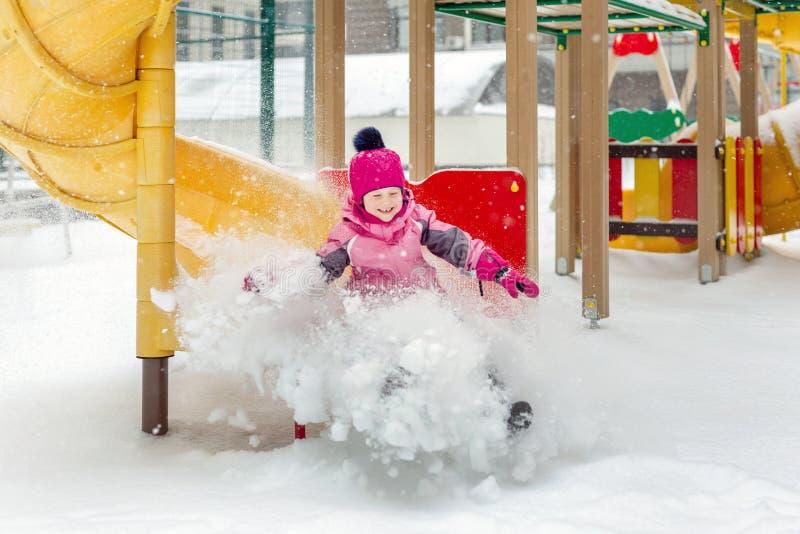 Λίγο χαριτωμένο κοριτσάκι που έχει τη διασκέδαση στην παιδική χαρά στο χειμώνα Χειμερινών αθλητισμού και ελεύθερου χρόνου παιδιών στοκ εικόνα