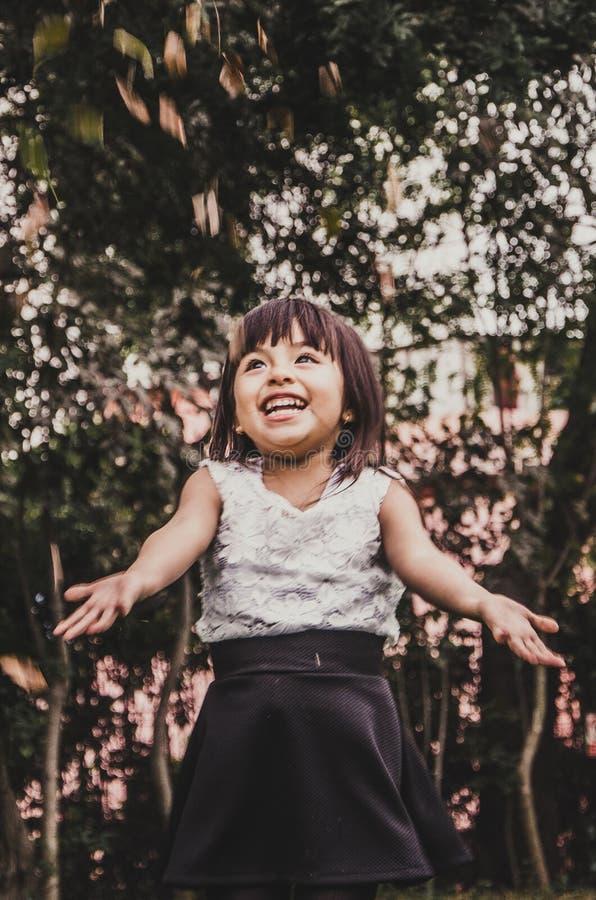 Λίγο χαριτωμένο με κοντά μαλλιά κορίτσι ρίχνει τα φύλλα στοκ εικόνα