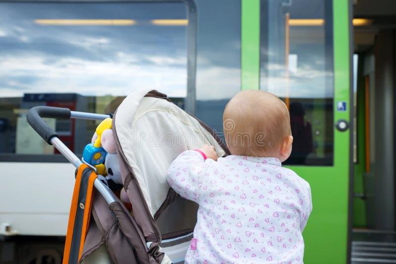 Λίγο χαριτωμένο μωρό εξετάζει την κλείνοντας πόρτα του τραίνου στοκ φωτογραφία με δικαίωμα ελεύθερης χρήσης